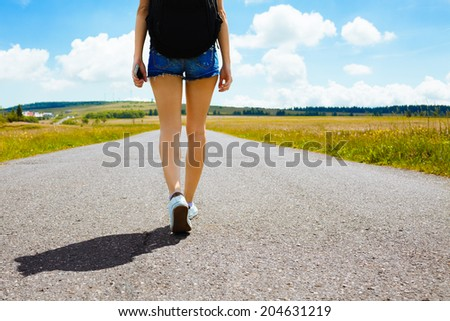 Woman walking down empty road on the country side. Adventure, sport and exercise.  - stock photo