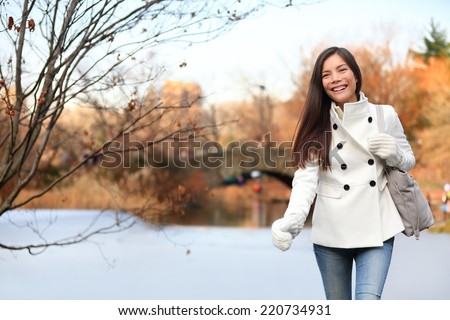 Woman walking happy in Central park, New York City in late fall early winter with skating rink in background. Candid smiling multi-ethnic girl on Manhattan, USA. - stock photo