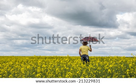 woman walking in a yellow canola field carrying an umbrella under a very dark cloudy day in the summer  - stock photo