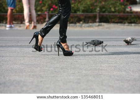 woman walking in high heels on the road next to pigeons - stock photo