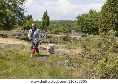 Woman walking in nature with her dog - stock photo