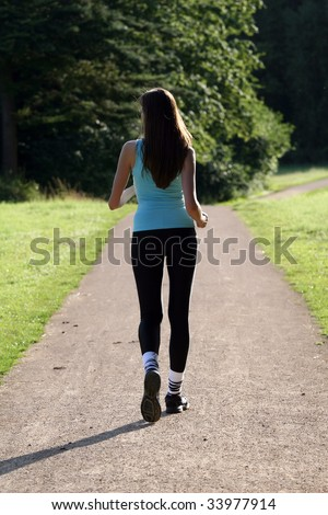 woman walking in park on the road - stock photo