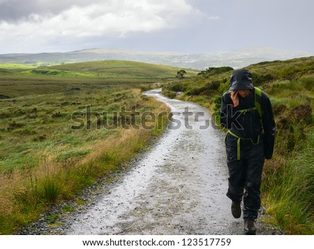 Woman walking in rain and talking on mobile phone