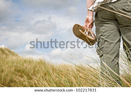 woman walking in sand dunes holding sandals - stock photo