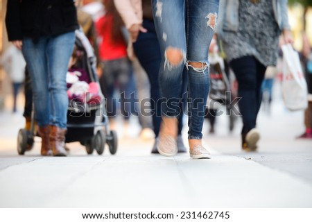 Woman walking in sidewalk crowd