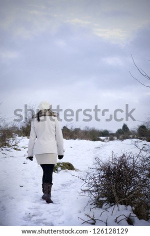 woman walking in snow covered fields - stock photo