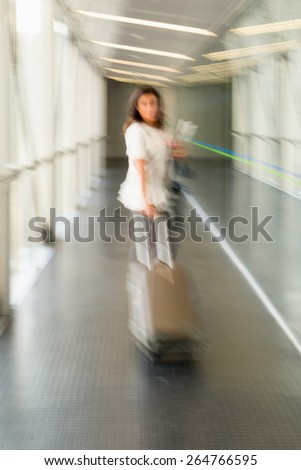 Woman walking in the corridor of an airport, pronounced motion blur - stock photo