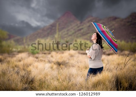 Woman Walking in the Desert During a Rain Storm. - stock photo