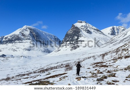 Woman walking in the mountains near Kebnekaise, Sweden, on a beautiful day in early spring.