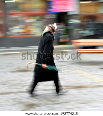 Woman walking in the street on a rainy day in motion blur