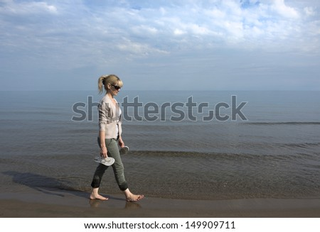Woman walking in water at shoreline holding sandals - stock photo