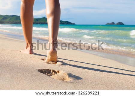 Woman walking on a beautiful Hawaii beach.