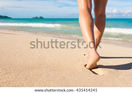 Woman walking on a beautiful white sand beach. Location Hawaii. - stock photo