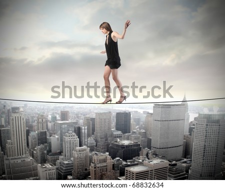 Woman walking on a rope over a cityscape - stock photo