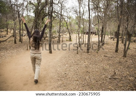 Woman walking on a safari trail in a dry forest. - stock photo
