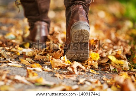 Woman walking on a street full of dead leaves during Autumn - stock photo