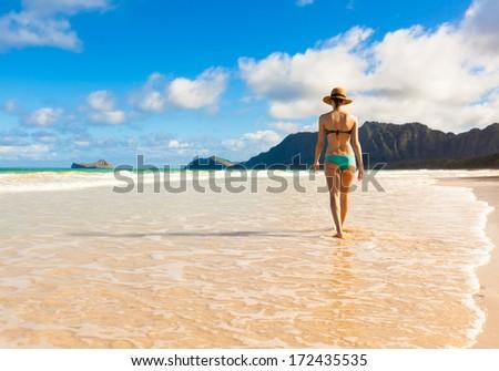 Woman walking on beautiful sand beach (Oahu, Hawaii) - stock photo