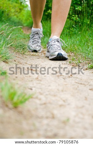 Woman walking on dirt footpath in forest, running and jogging sport shoes - stock photo
