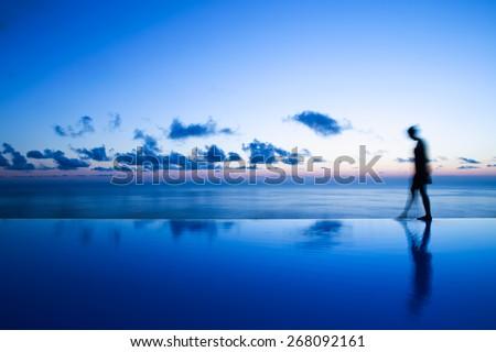 Woman walking on edge of infinity pool - stock photo
