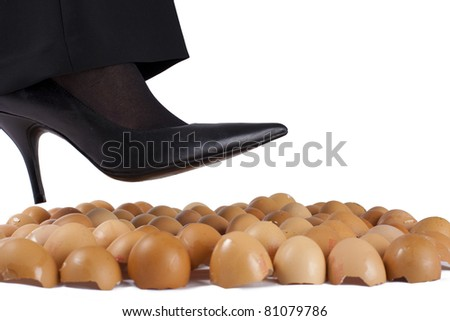 Woman walking on egg shells in high heels, white background. - stock photo