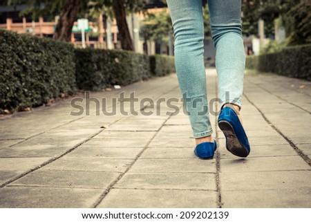 Woman walking on foot path. Vintage filter. - stock photo