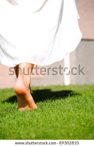 woman walking on grass bare feet - stock photo