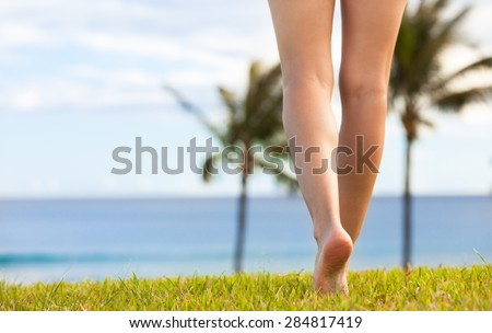 Woman walking on grass barefoot towards the beach.