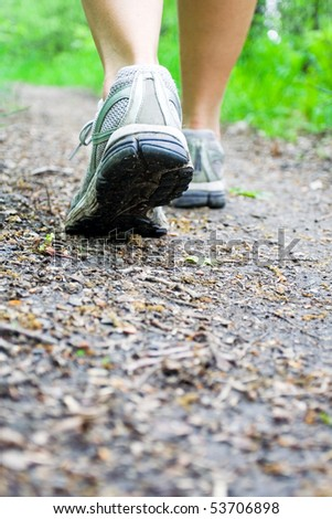 Woman walking on hiking trail in forest - stock photo