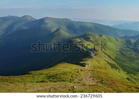 Woman walking on mountain terrain on a sunny day  - stock photo