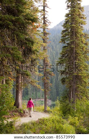Woman Walking on Remote Lakeside Trail - stock photo
