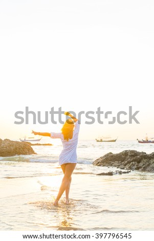 woman walking on sand beach at golden hour - stock photo
