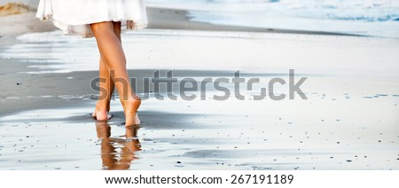 Woman walking on sand beach leaving footprint in the sand - stock photo