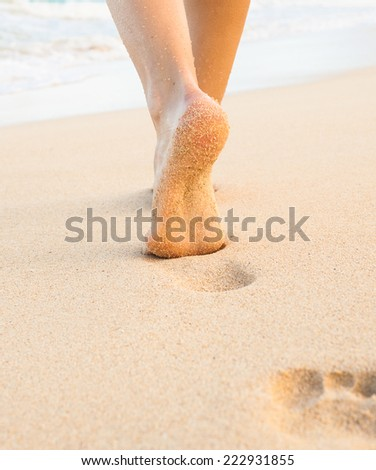 Woman walking on sand beach leaving footprints in the sand. Closeup detail of female feet and golden sandy beach in Hawaii - stock photo