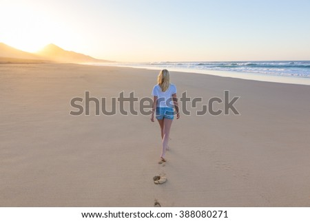 Woman walking on sandy beach in sunset leaving footprints in the sand. Beach, travel, concept. Copy space. - stock photo