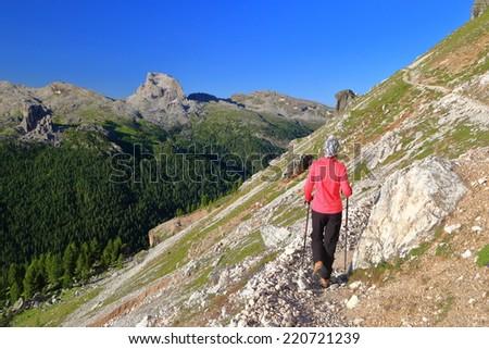 Woman walking on steep slope along Tofana range, Dolomite Alps, Italy - stock photo
