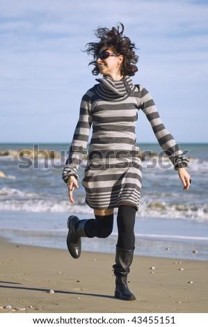 Woman walking on the beach. - stock photo