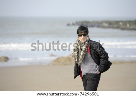 woman walking on the beach - stock photo
