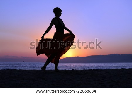 Woman walking on the beach at sunset - stock photo