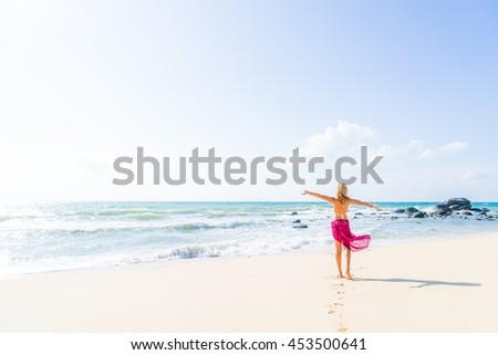 woman walking on the sand beach - stock photo