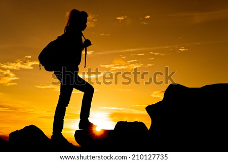 Woman walking on top of mountain at twilight with sun ray under her feet