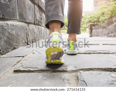 Woman walking on trail outdoor with sunlight - stock photo