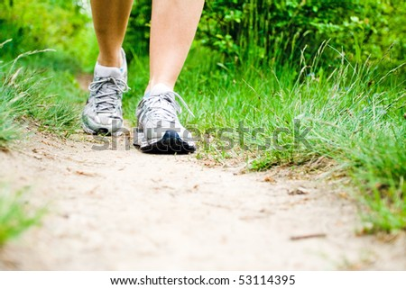 Woman walking on trail path on meadow or forest. Jogging or training outside in summer nature, motivational health and fitness concept. - stock photo