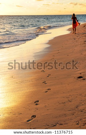 Woman walking on tropical beach at sunrise - stock photo