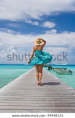 woman walking on tropical cruise ship pier in sarong blowing in wind - stock photo