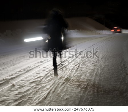Woman walking on winter road at night, with cars in blurred motion - stock photo