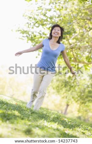 Woman walking outdoors smiling - stock photo