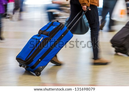 Woman walking quickly pulling blue luggage in busy airport - stock photo