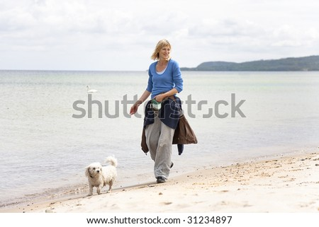 Woman walking the dog on the beach - stock photo