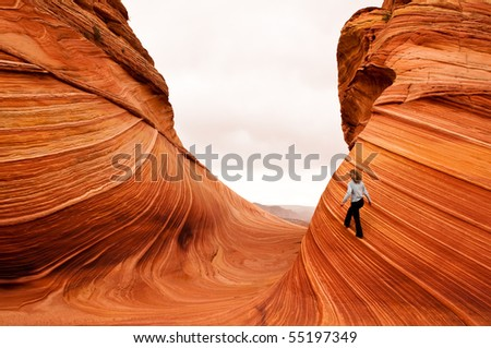 Woman walking the Fine Line on vertical multi-layered sandstone landmark, The Wave