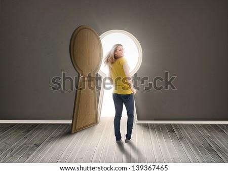 Woman walking towards keyhole shaped doorway with light dark grey room - stock photo